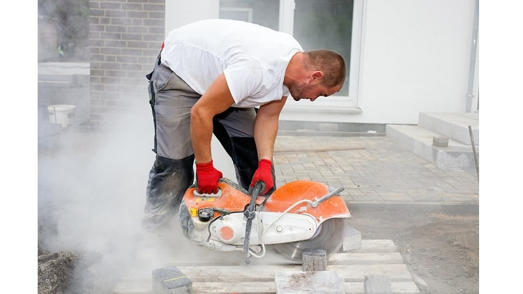 Construction worker using a concrete saw cutting stones in a cloud of concrete dust for creating a track.