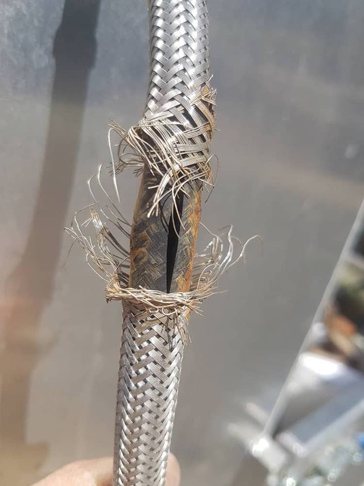 The stainless steel braided sleeve corrodes, causing the rubber inner tube to expand and burst. Image supplied by Neil & Craig Baker Plumbing - NSW.